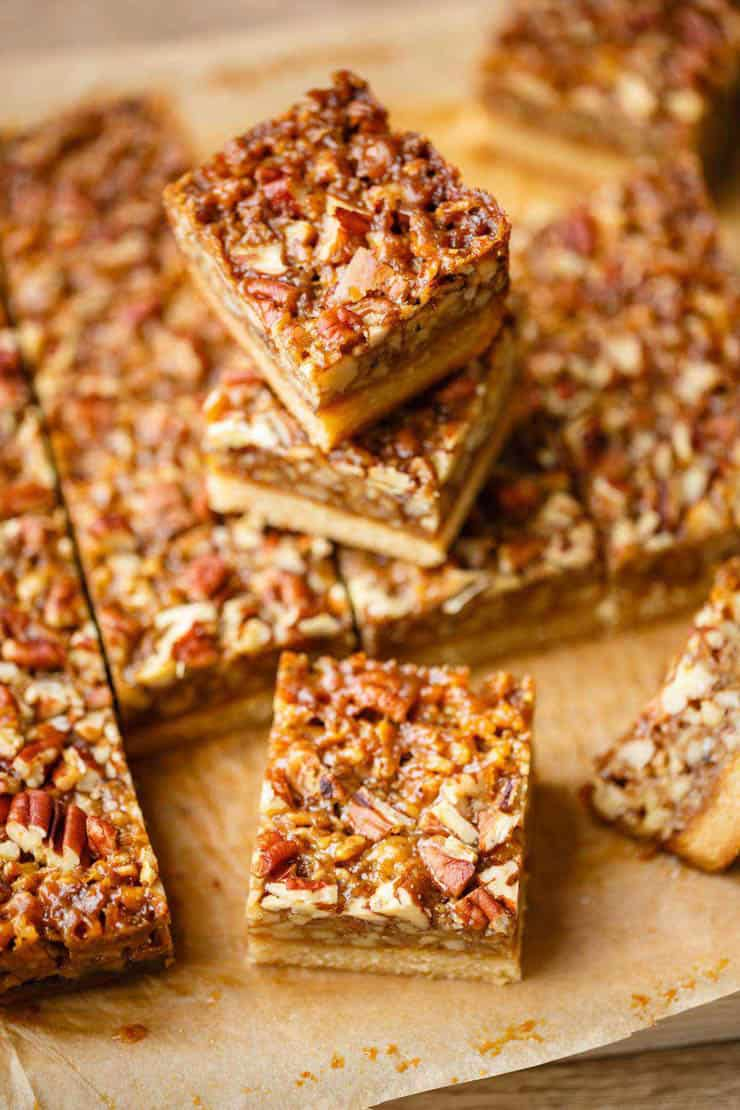 Pecan bars cut into squares on a wooden surface