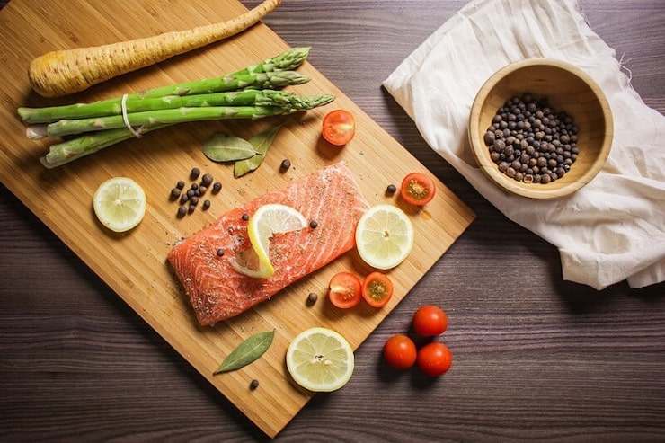 an overhead shot of a salmon fillet on a wooden board topped with a slice of lemon and vegetables around it