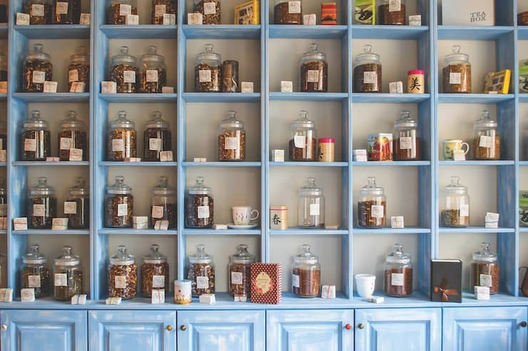 Wall shelf with various glass jars of herbs