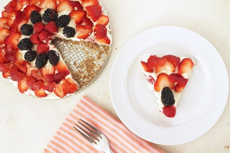 A No Bake Fruit Tart on a plate with a slice cut out sitting on a white plate