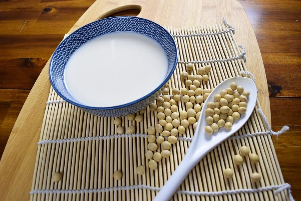 A bowl of milk sitting on a wooden table with soy beans at the side