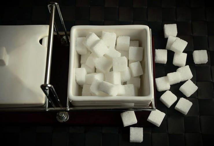 An overhead shot of sugar cubes in a white ramekin