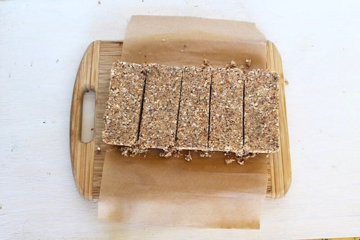 Sliced slab of homemade paleo protein bars without chocolate on parchment paper on a wooden cutting board on a white wooden surface