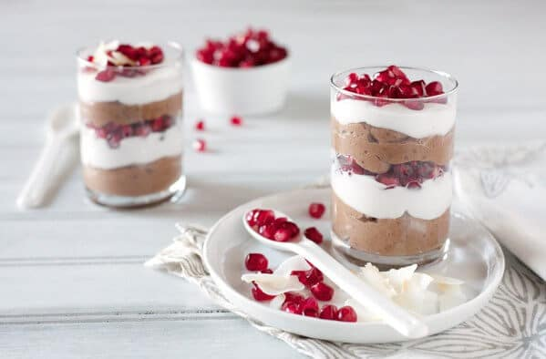 Layered chocolate, coconut pudding and pomegranate seeds in a clear glass on a white table