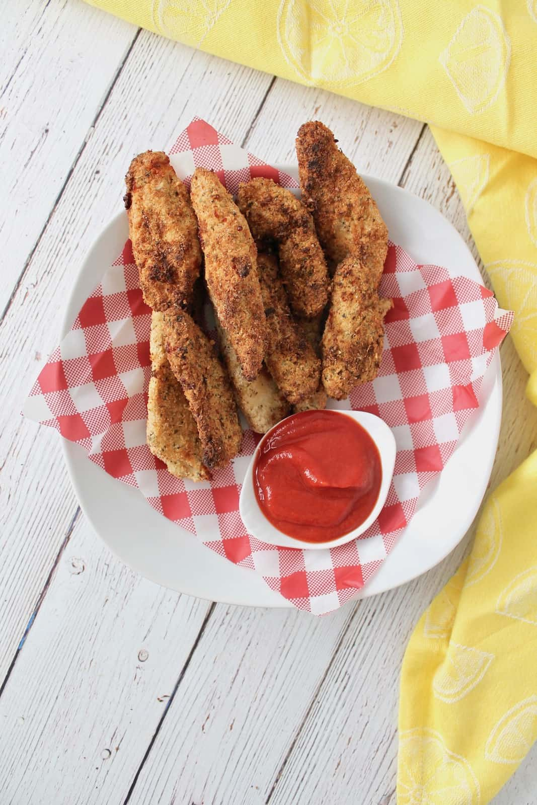 Overhead shot of finished chicken fingers in a white shallow bowl lined with red and white checkered picnic paper with a white dish of ketchup in the bowl on a white wooden surface with a yellow dish towel next to it
