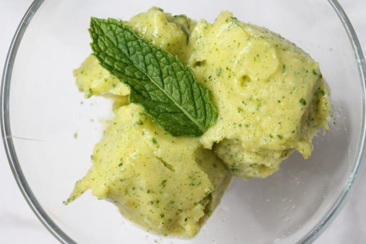 three scoops of yellow pineapple sorbet with green mint flecks in it topped with green mint leaf