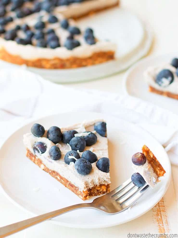 One slice of blueberry tart on a white plate with whole tart in background