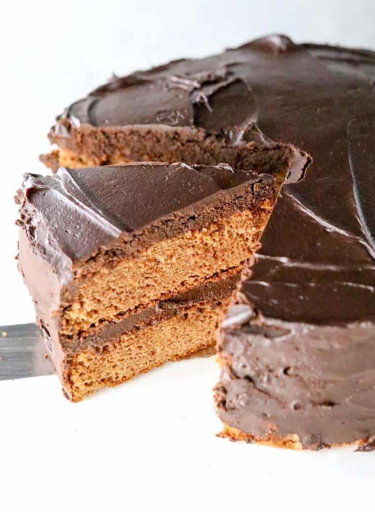 Whole vanilla cake with chocolate frosting with a slice being taken out of it
