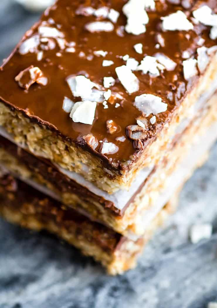 three stacked cashew bars with a layer of chocolate on top sprinkled with coconut