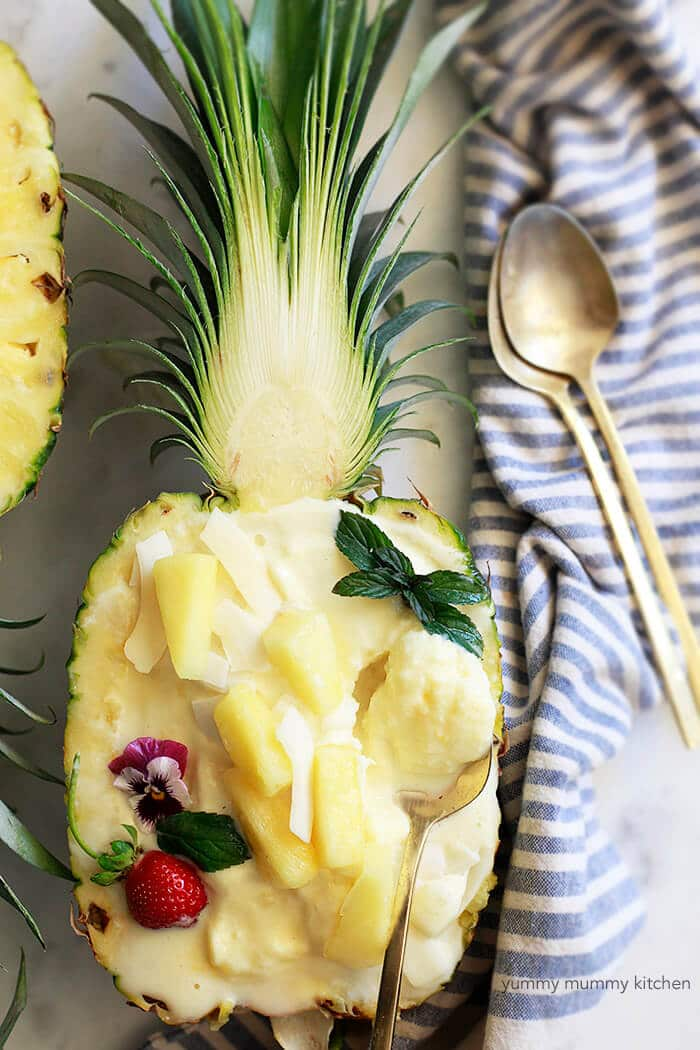 halved pineapple with scooped out flesh with pineapple ice cream inside