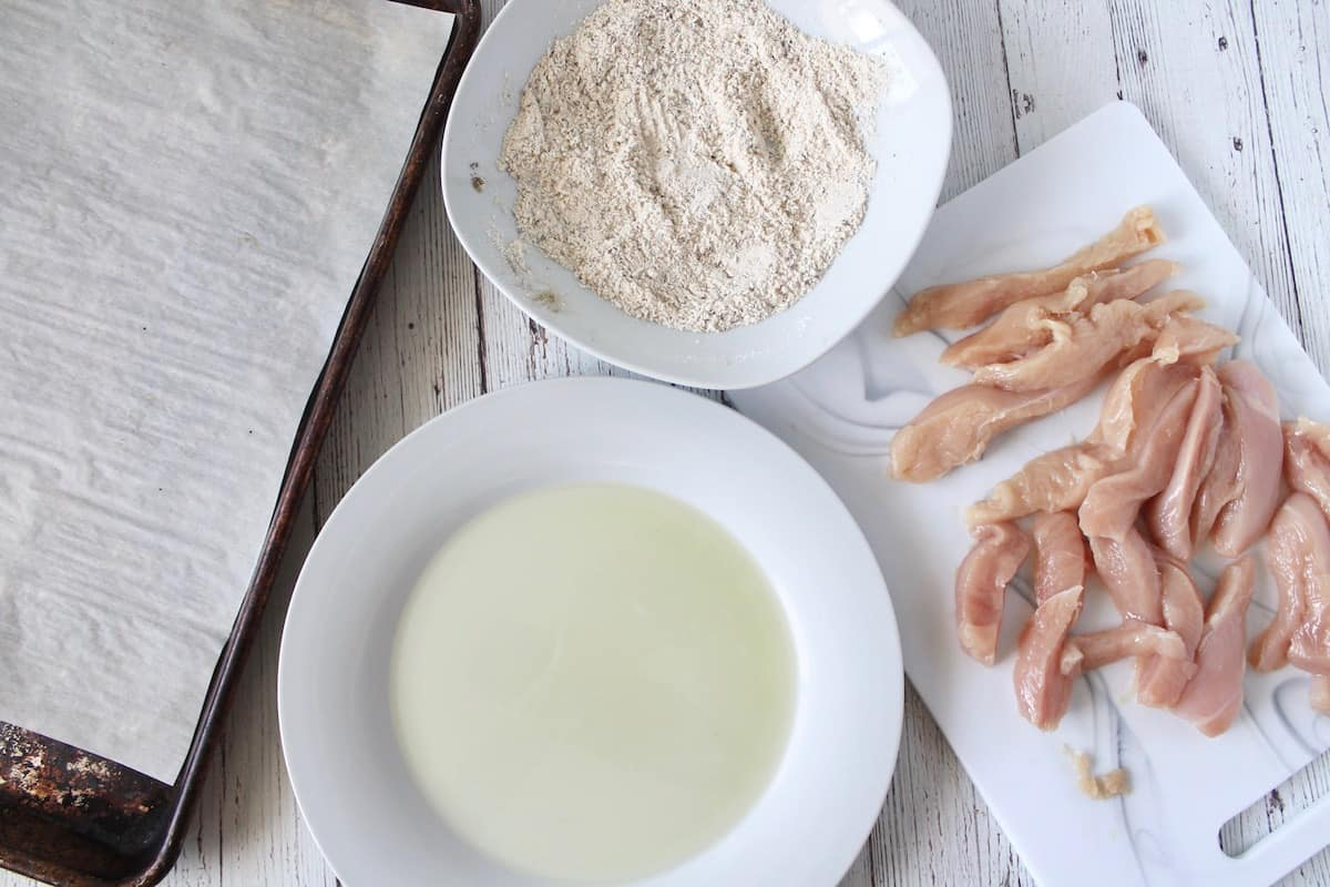 Overhead shot of raw chicken breast on a white cutting board next to a plate of oil, a bowl of flour mixture and a baking sheet lined with parchment paper