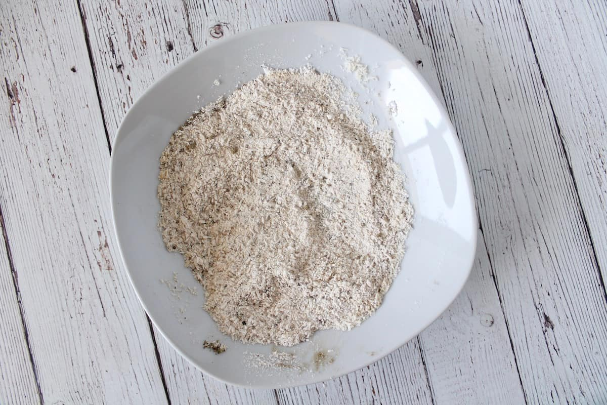 Overhead shot of a white shallow bowl with a whitish flour mixture in it on a white wooden surface