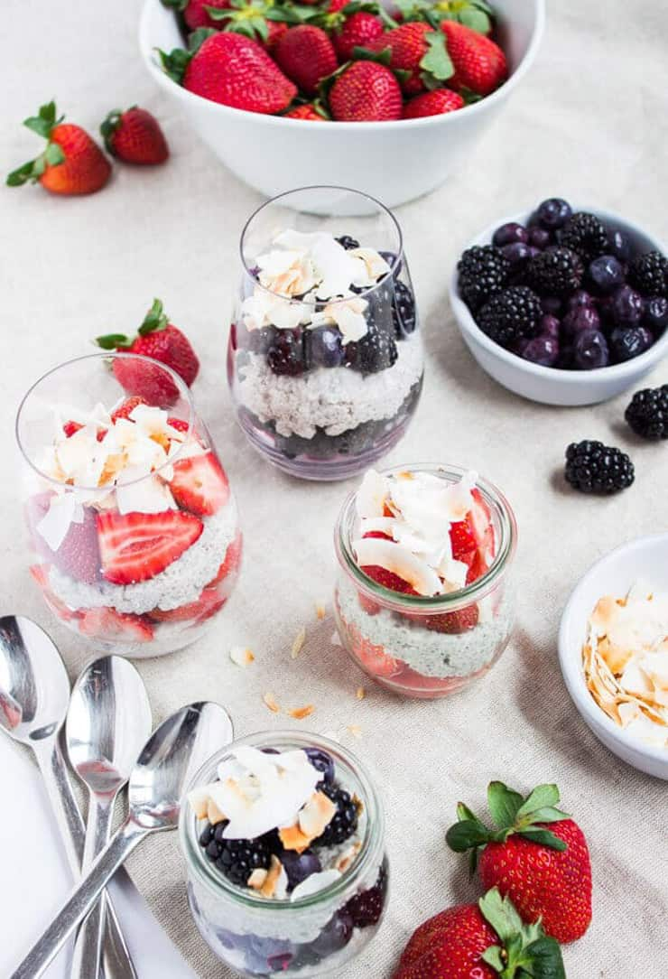 Three glasses on chia parfaits on a white table with fresh fruit