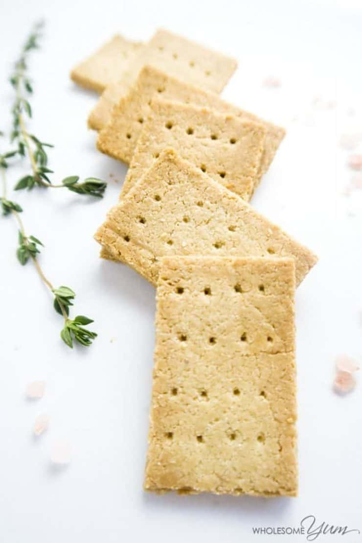 A small pile of paleo crackers lying next to some thyme sprigs