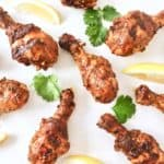 Cooked chicken tandoori on a white surface next to cilantro and sliced lemons