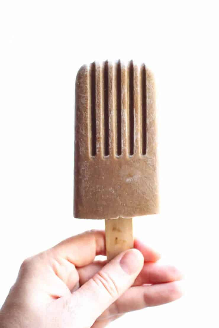 A healthy ice cream Popsicle being held with a white background