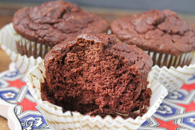 A close up of chocolate muffins with a bite out