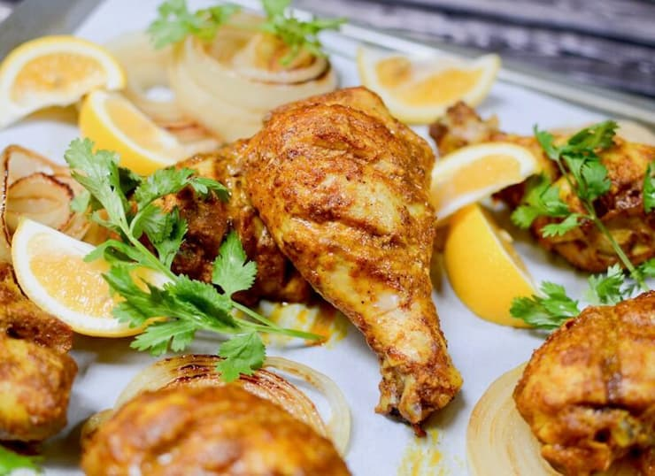 Tandoori chicken on a baking tray with slices of lemon and herbs