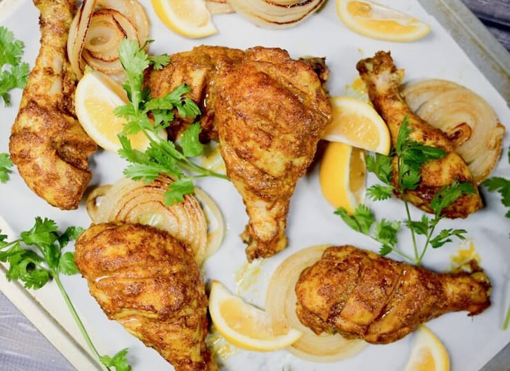 Tandoori chicken on a baking tray with wedges of lemon and herbs