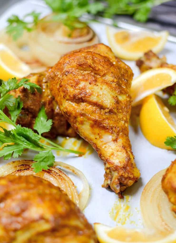A close up of tandoori chicken on a baking tray with lemon and herbs scattered around
