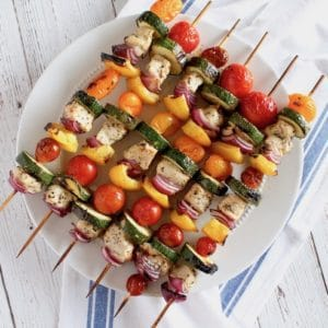 overhead view of cooked chicken kabobs on a white plate with white cloth with blue stripe underneath