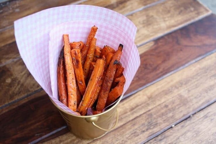 A pot of carrot fries sitting on a wooden surface