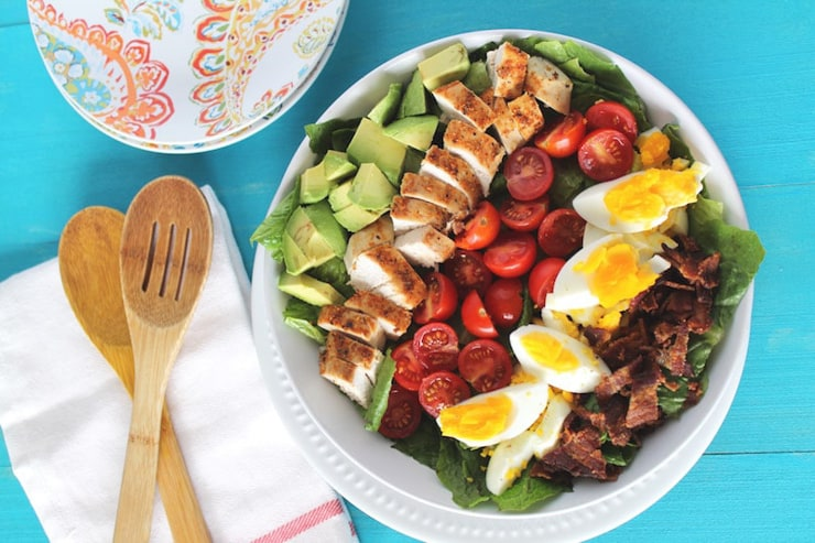 An overhead shot of a cobb salad with salad servers at the side