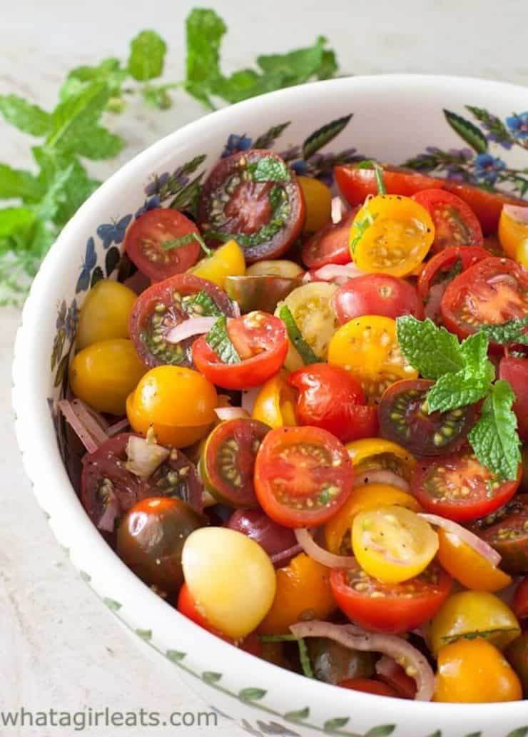A chopped tomato salad in a white bowl topped with herbs