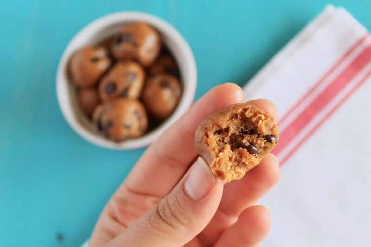 A hand holding a chocolate chip energy ball with a bite out