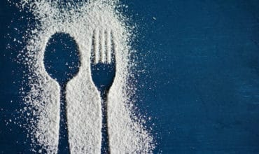 An outline of a spoon and fork dusted with sugar on a blue surface