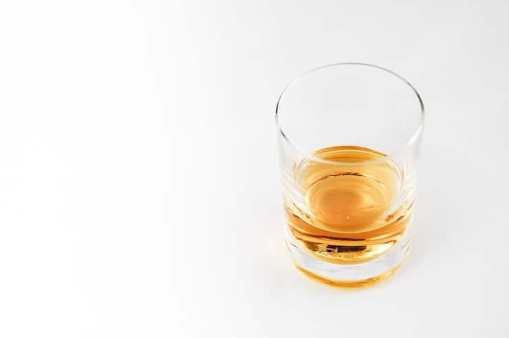 A photo of whiskey in a small glass sitting on a white surface