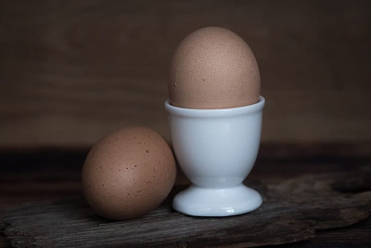 Two eggs one in an egg cup and one beside it sitting on a wooden surface