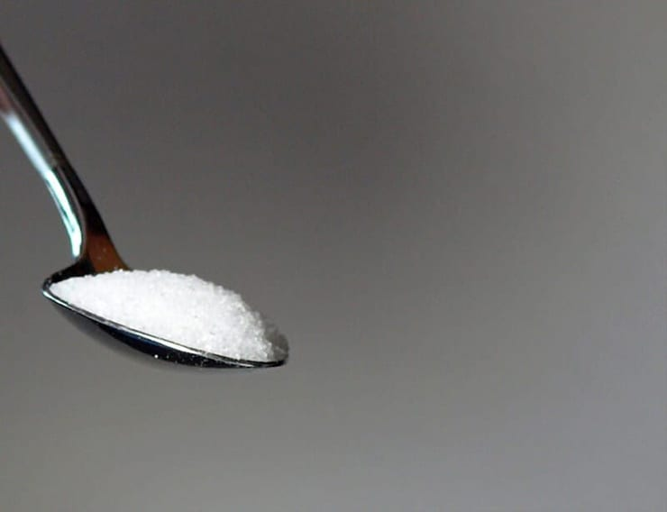 A photo of a teaspoon of sugar with a grey background