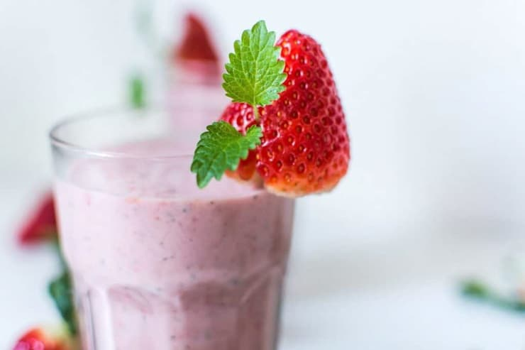 A strawberry smoothie garnish with a strawberry at the side