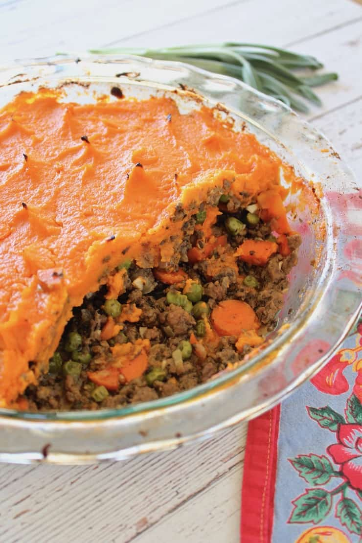 Close up of shepherd's pie in a clear pie dish with pieces taken out of it