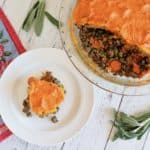 overhead view of shepherd's pie with pieces taken out of it and a slice on a separate white plate