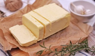 Stick of butter on brown wax paper next to rosemary
