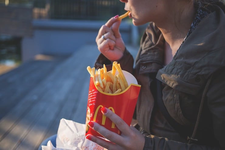 woman eating french fries from red mcdonalds container