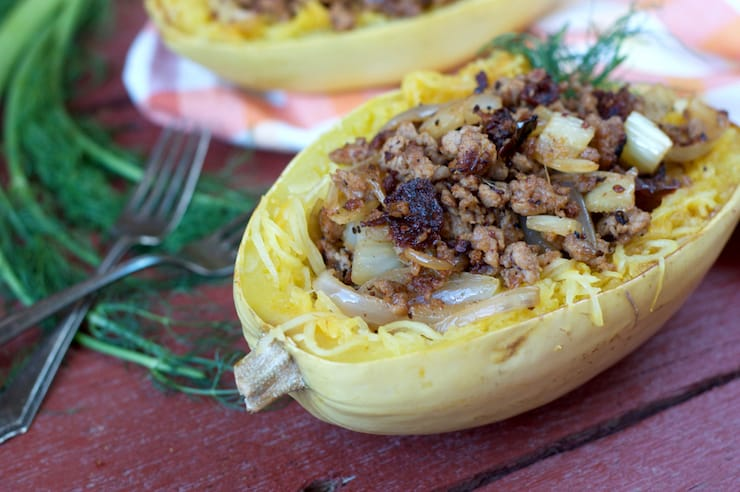 Halved cooked spaghetti squash with sausage mixture inside on wooden table