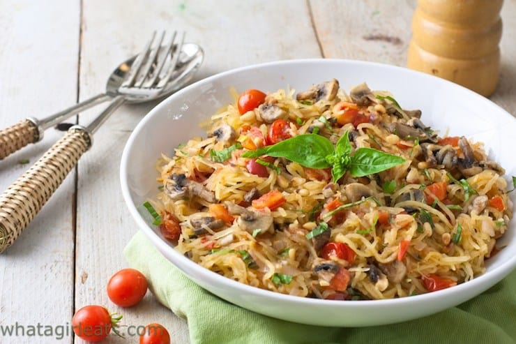 White bowl filled with spaghetti squash with mushrooms tomato and basil