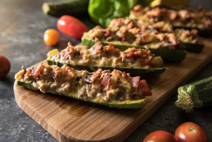 A close up of zucchini stuffed with meat on a wooden board