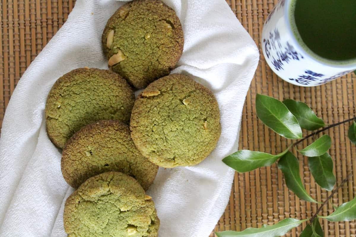 Five matcha green tea cookies on a white surface with a small mug of green matcha tea on the side