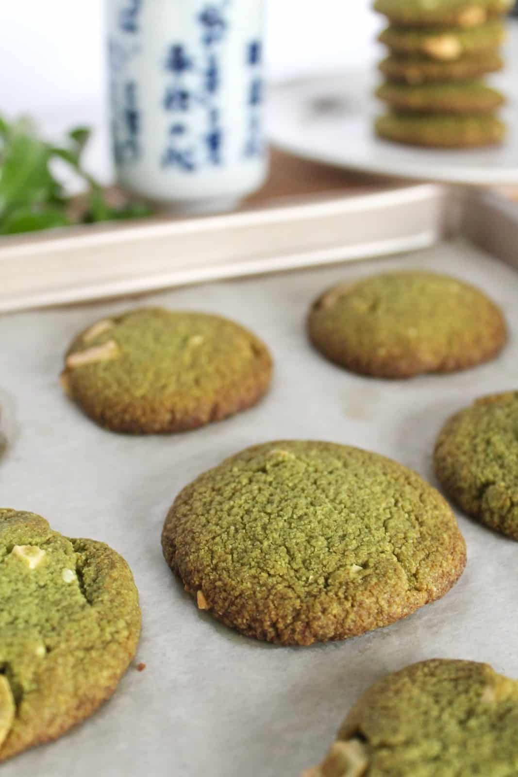 Close up of finished green cookies on a baking sheet lined with parchment paper