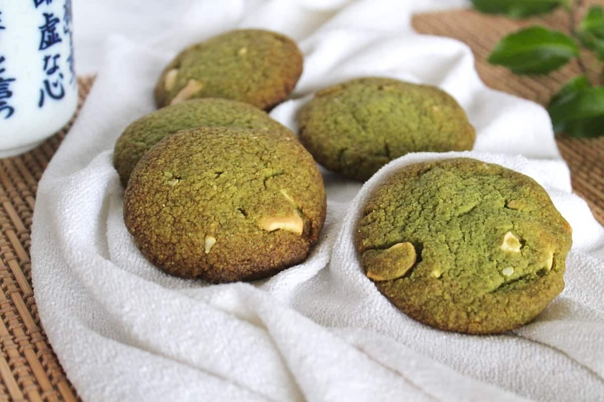 Close up of four green matcha cookies on a white towel on a wood slat mat next to a cup of green tea