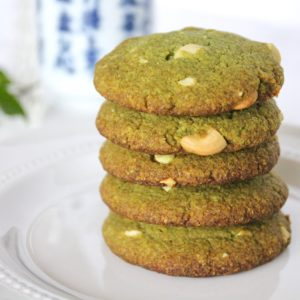 Five stacked matcha green tea cookies on a white plate with a cup of green tea and green leaves in the background