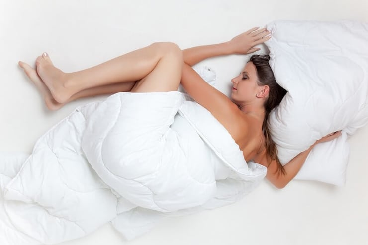 A woman sleeping in a bed with white bed covers and pillows