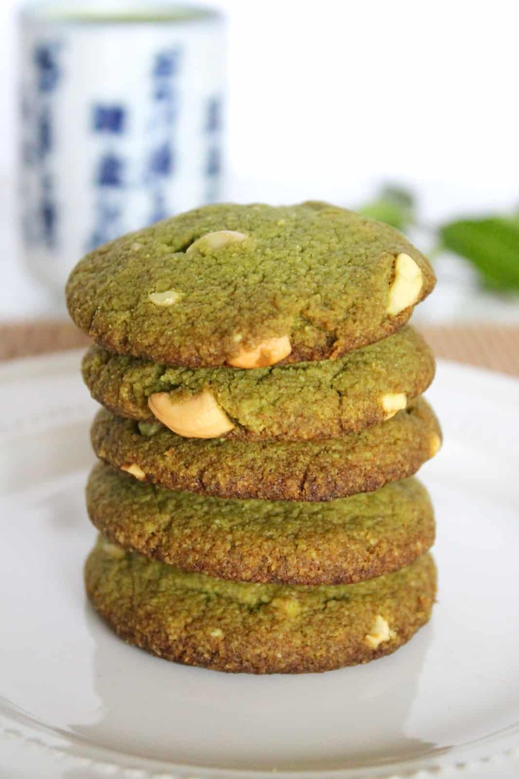 Close up of five stacked matcha green tea cookies on a white plate with a mug of green tea and green leaves in the background