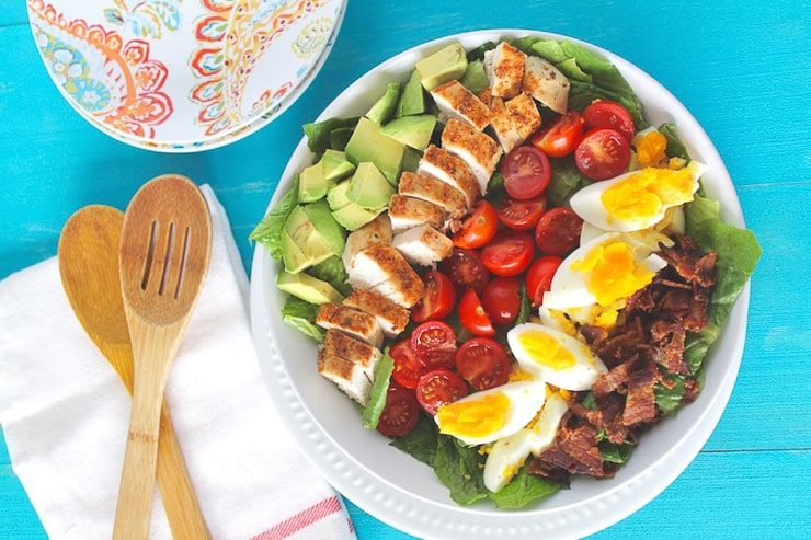 A cobb salad on a plate with a blue background
