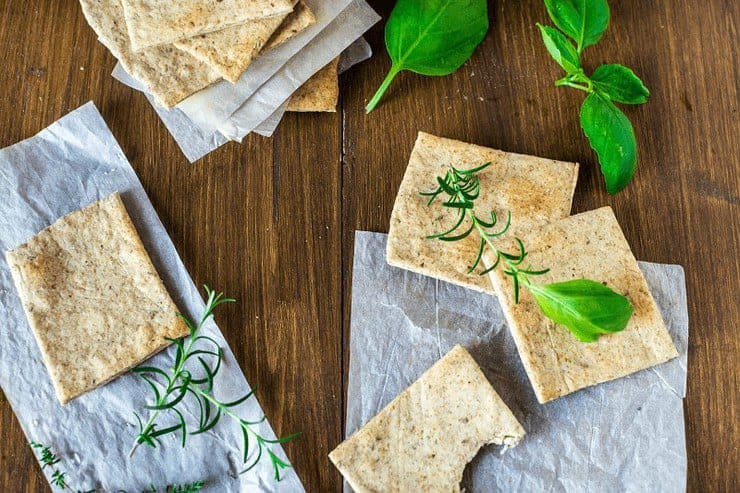 Crackers on a wooden surface topped with herbs and baking paper