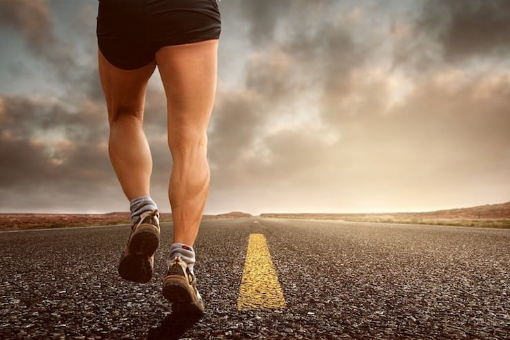 close up of man's legs running on an asphalt road